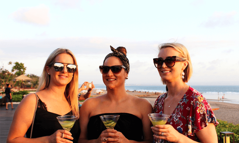 1000 Mile Travel Experts Marnie, Tia and Emily enjoying sundown cocktails by the beach at the Alila Seminyak